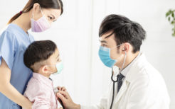 medical doctor wear mask  and examining  little boy  in clinic