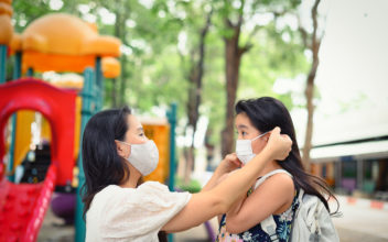 Mother puts a safety mask on daughter face for protection Covid-19 or coronavirus outbreak in village park to prepare go to school. Back to school concept. Medical mask to prevent coronavirus.